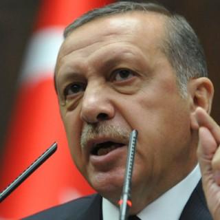 Recep Tayyip Erdogan redet am Mikrofon. Im Hintergrund die türkische Fahne zu erkennen.