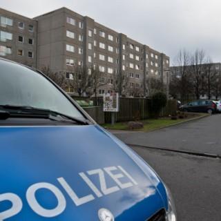 Ein Polizeifahrzeug steht am 14.01.2015 vor einem Plattenbau an der Johannes-Paul-Thilman-Straße im Stadtteil Dresden-Leubnitz-Neuostra. Ein 20 Jahre alter Eritreer, der tot im Hof gefunden wurde, ist getötet worden, wie Medien unter Berufung auf den Polizeipräsidenten berichten.